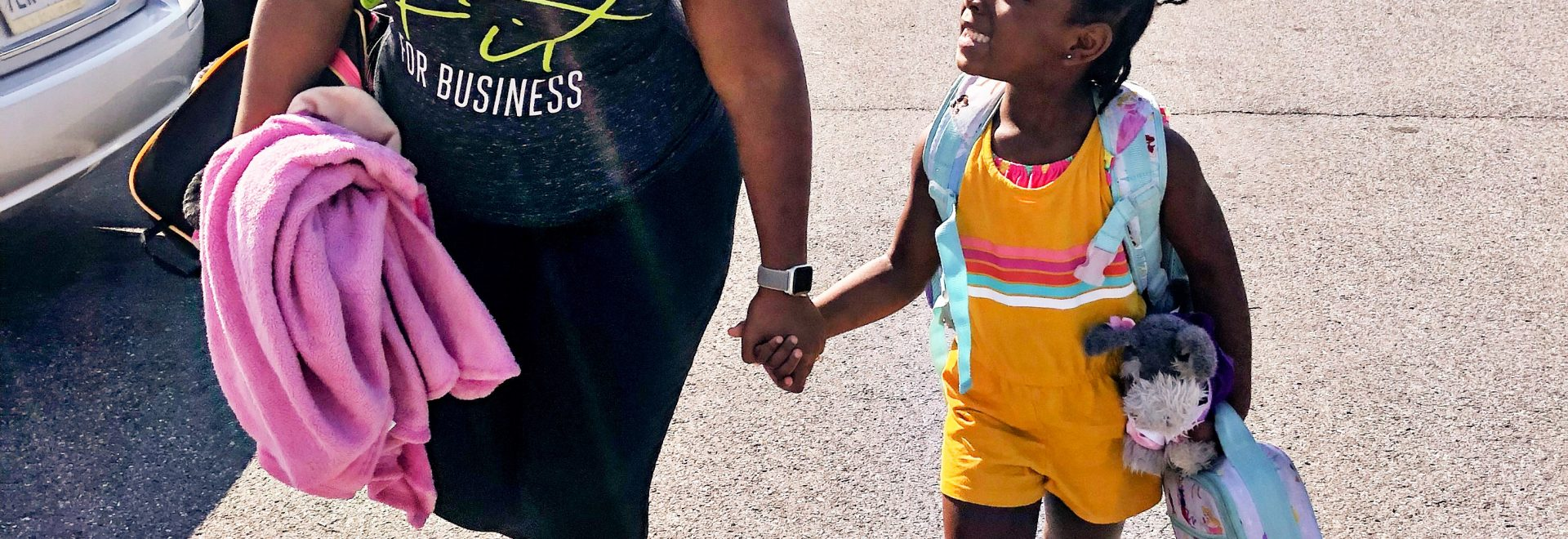 mom and daughter smiling while walking and holding hands