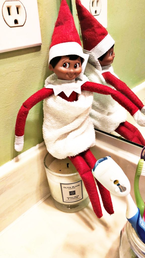 Elf on the Shelf sits alongside the bathroom sink wrapped in a mini towel